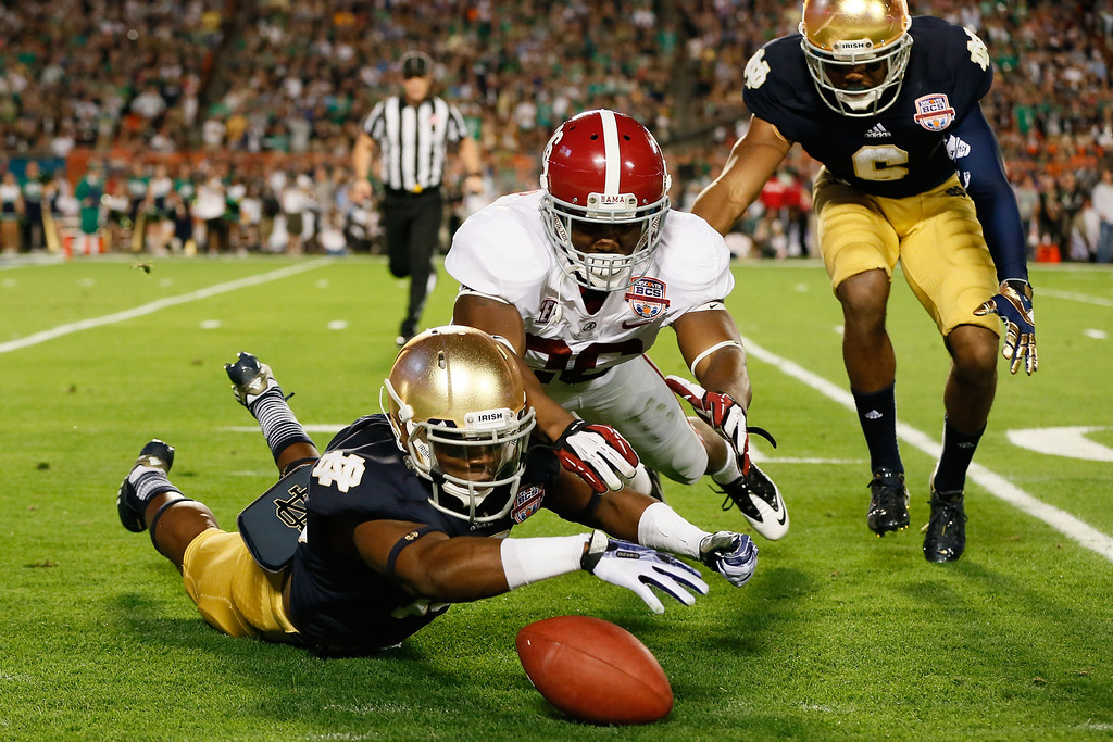 Description of . MIAMI GARDENS, FL - JANUARY 07:  Davonte' Neal #19 of the Notre Dame Fighting Irish fights for a loose ball after muffing the punt against Landon Collins #26 of the Alabama Crimson Tide in the second quarter against the Alabama Crimson Tide during the 2013 Discover BCS National Championship game at Sun Life Stadium on January 7, 2013 in Miami Gardens, Florida.  (Photo by Kevin C. Cox/Getty Images)