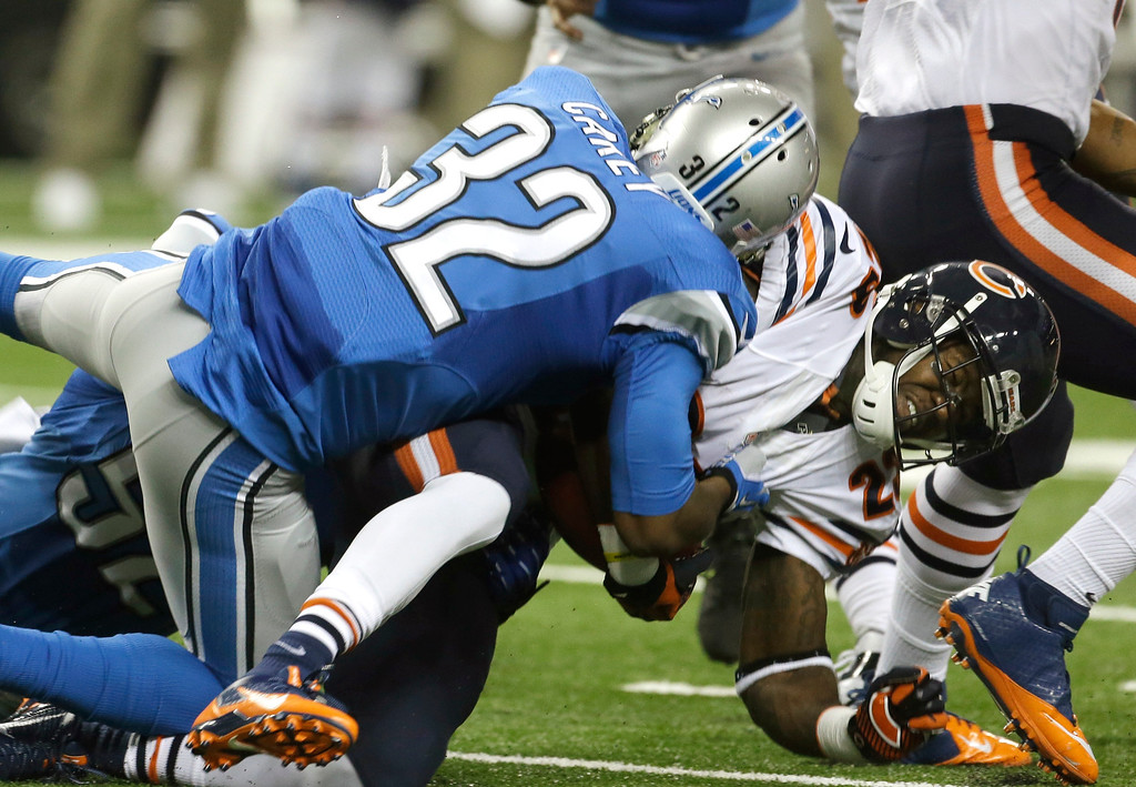 Description of . Chicago Bears running back Matt Forte (22) is stopped by Detroit Lions strong safety Don Carey (32) during the first quarter of an NFL football game at Ford Field in Detroit, Sunday, Sept. 29, 2013. (AP Photo/Carlos Osorio)