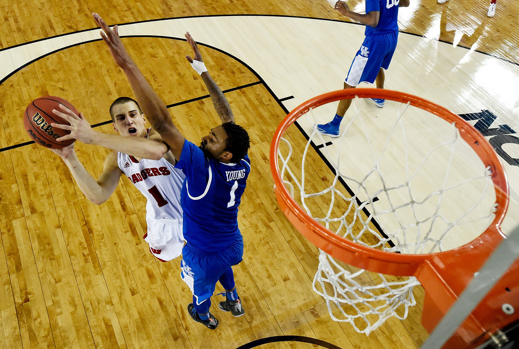 Description of . ARLINGTON, TX - APRIL 05: Ben Brust #1 of the Wisconsin Badgers goes to the basket as James Young #1 of the Kentucky Wildcats defends during the NCAA Men's Final Four Semifinal at AT&T Stadium on April 5, 2014 in Arlington, Texas. (Photo by Chris Steppig-Pool/Getty Images)