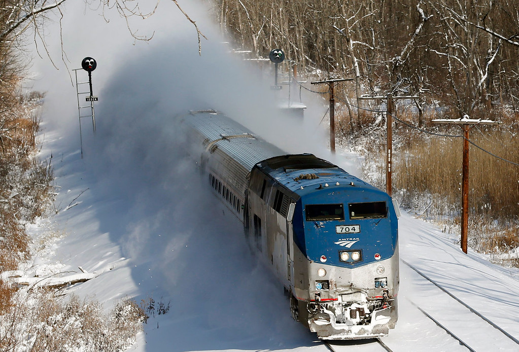 Description of . An Amtrak train kicks up fresh snow as it speeds southbound on Friday, Jan. 3, 2014, in Schodack Landing, N.Y. The National Weather Service has posted winter storm warnings through Friday morning in most of the state. Temperatures are in the single digits or below zero, with the wind making it feel as cold as 20-30 below zero in some areas. (AP Photo/Mike Groll)