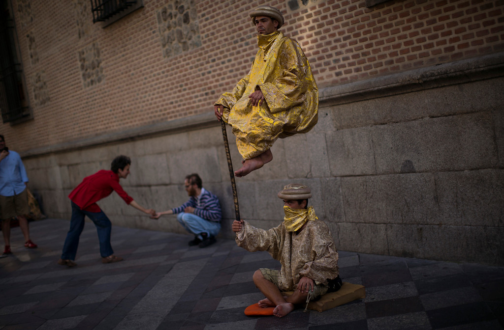 Description of . Men performance as they beg for charity in a street in Madrid, Spain,  Monday, May 14, 2012. Spain got caught up in the uncertainty surrounding the European single currency and the electoral stalemate in Greece Monday as it saw its borrowing costs rise and stock prices fall at alarming rates. (AP Photo/Emilio Morenatti)