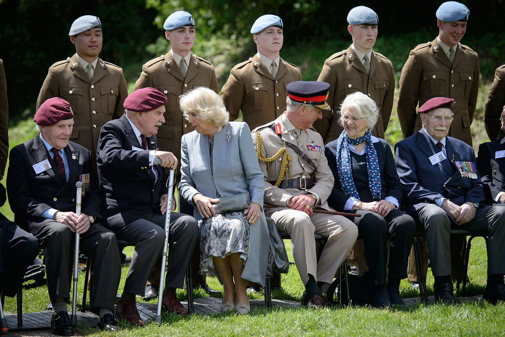Description of . Britain's Prince Charles, center right, and the Duchess of Cornwall Camilla, center left, meet glider pilot veterans during a D-Day commemoration event at the Pegasus bridge, in Benouville, western France, Thursday, June 5, 2014, marking the 70th anniversary of the World War II Allied landings in Normandy. (AP Photo/Leon Neal, pool)