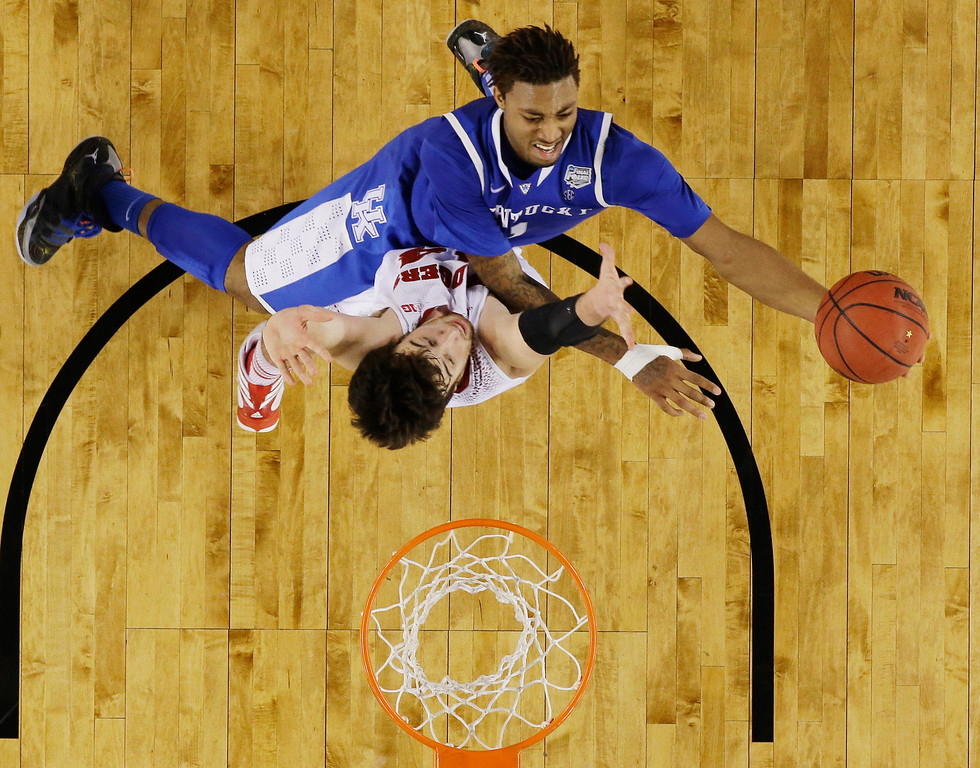 Description of . Kentucky guard James Young shoots against Wisconsin forward Frank Kaminsky during the second half of the NCAA Final Four tournament college basketball semifinal game Saturday, April 5, 2014, in Arlington, Texas. (AP Photo/David J. Phillip)