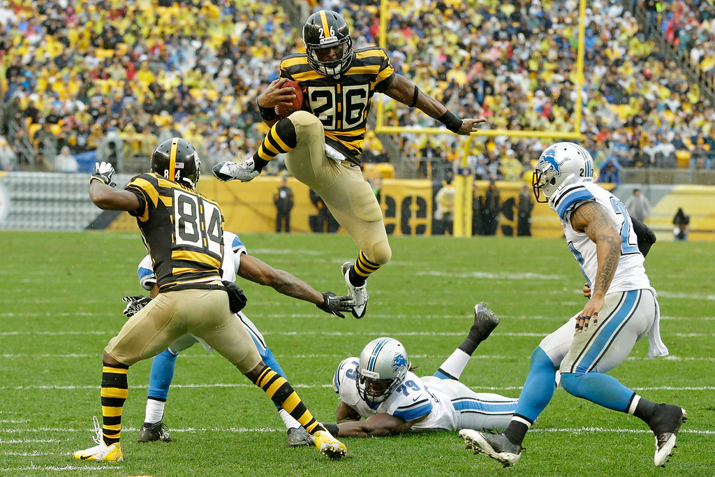 Description of . Pittsburgh Steelers running back Le'Veon Bell (26) leaps for more yardage as he tries to evade Detroit Lions strong safety Glover Quin (27) and the defense in the first half of an NFL football game in Pittsburgh, Sunday, Nov. 17, 2013. (AP Photo/Gene J. Puskar)