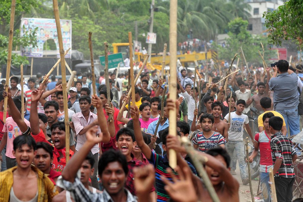 Description of . Garment workers shout slogans as they block a street during a protest to demand capital punishment for those responsible for the collapse of the Rana Plaza building in Savar, outside Dhaka April 30, 2013. REUTERS/Khurshed Rinku