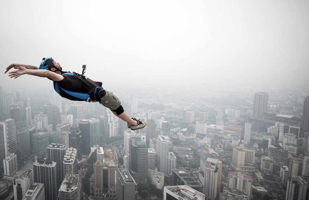 Description of . Base jumper Julien Dominique Briquez from France leaps from the 300-metres Open Deck of the Malaysia's landmark Kuala Lumpur Tower during the International Tower Jump in Kuala Lumpur on September 27, 2013.    AFP PHOTO / MOHD RASFANMOHD RASFAN/AFP/Getty Images