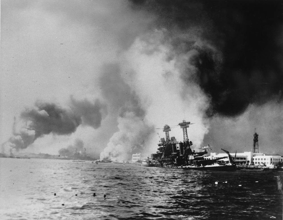 Description of . Struck by two battleships and two big bombs, the USS California, right, settles to the bottom during the Japanese sneak attack on Pearl Harbor on Dec. 7, 1941 during World War II. (AP Photo)