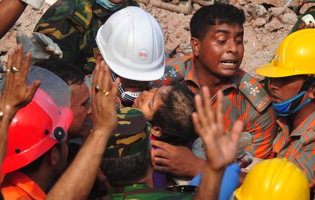 Description of . Rescuers carry a survivor pulled out from the rubble of a building that collapsed in Savar, near Dhaka, Bangladesh, Friday, May 10, 2013. (AP Photo)