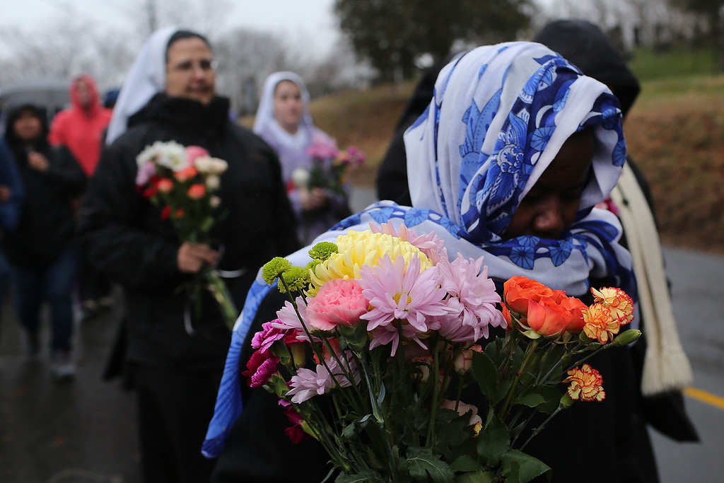 Description of . NEWTOWN, CT - DECEMBER 16:  Members of Sisters of Christian Charity walk to lay flowers in front of the Sandy Hook School December 16, 2012 in Newtown, Connecticut. Twenty-six people were shot dead, including twenty children, after a gunman identified as Adam Lanza opened fire at Sandy Hook Elementary School. Lanza also reportedly had committed suicide at the scene. A 28th person, believed to be Nancy Lanza, found dead in a house in town, was also believed to have been shot by Adam Lanza.  (Photo by Spencer Platt/Getty Images)