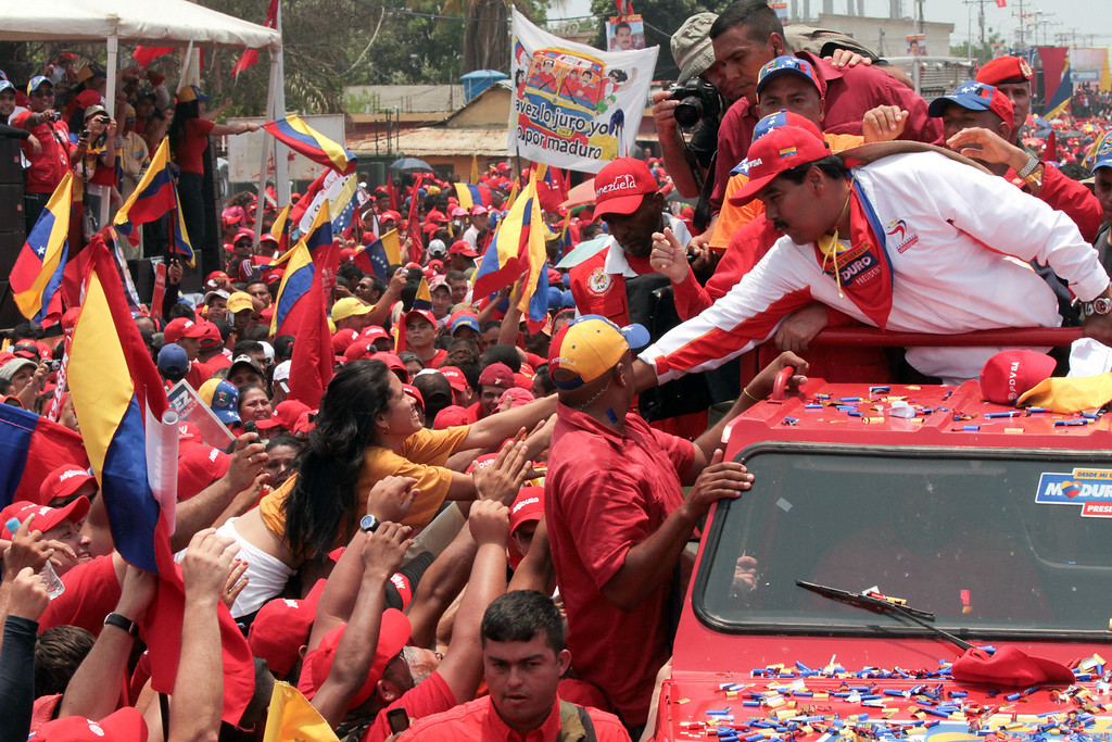 Description of . In this photo released by Miraflores Press Office, Venezuela's acting President Nicolas Maduro greets supporters as he campaigns in Cabimas, Zulia state, Venezuela,  Thursday, April 11, 2013. Maduro, late President Hugo Chavez's hand-picked successor, will run for president against opposition candidate Henrique Capriles on April 14. (AP Photo/Miraflores Press Office)