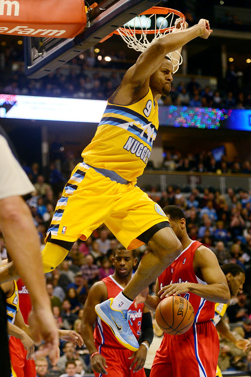 Description of . Denver Nuggets shooting guard Andre Iguodala (9) comes off the rim after dunking the ball against the Los Angeles Clippers during the first half at the Pepsi Center on Tuesday, January 1, 2013. AAron Ontiveroz, The Denver Post
