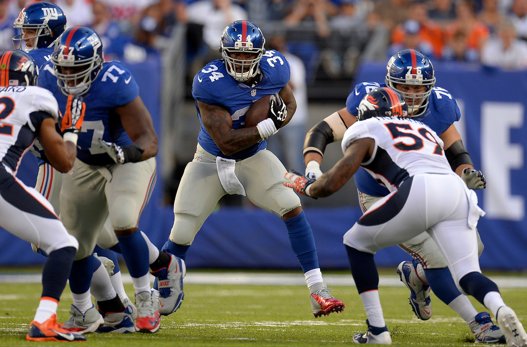 Description of . New York Giants running back Brandon Jacobs (34) find a hole in the Denver Broncos defense during the second quarter September 15, 2013 MetLife Stadium. (Photo by John Leyba/The Denver Post)