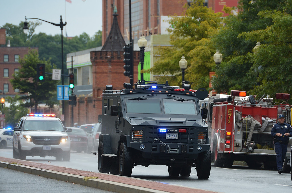 Description of . An armored personnel carrier speeds down M Street, SE away from the Washington Navy Yard on September 16, 2013 in Washington, DC.  At least one unidentified gunman opened fire at the US Navy Yard in Washington on Monday and was at large after killing