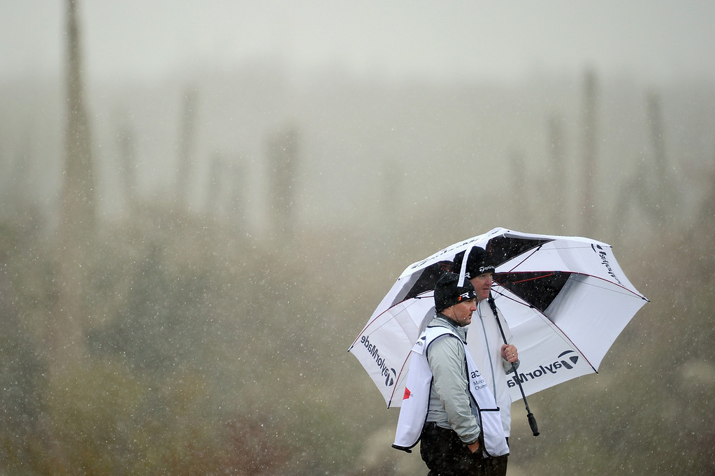 Description of . MARANA, AZ - FEBRUARY 20:  Marcus Fraser of Australia stands under an umbrella with his caddie as snow and rain fall during the first round of the World Golf Championships - Accenture Match Play at the Golf Club at Dove Mountain on February 20, 2013 in Marana, Arizona.  (Photo by Stuart Franklin/Getty Images)