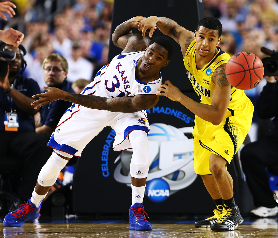 Description of . ARLINGTON, TX - MARCH 29:  Jamari Traylor #31 of the Kansas Jayhawks and Trey Burke #3 of the Michigan Wolverines vie for a looseball in the second half during the South Regional Semifinal round of the 2013 NCAA Men\'s Basketball Tournament at Dallas Cowboys Stadium on March 29, 2013 in Arlington, Texas.  (Photo by Tom Pennington/Getty Images)