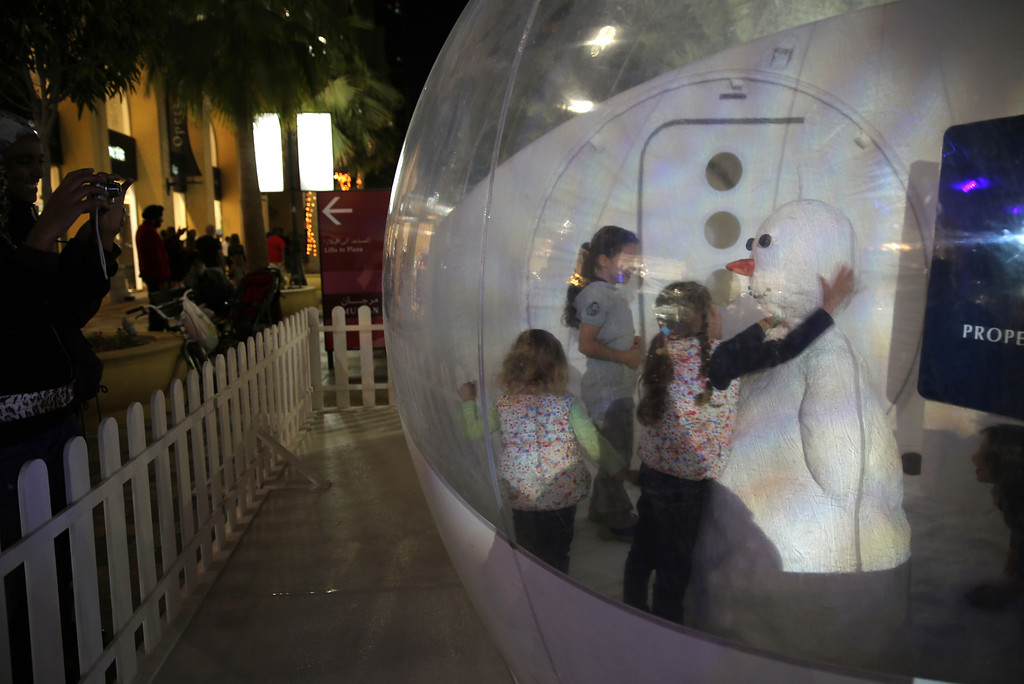 Description of . Girls play with a snowman inside a plastic ball covered with artificial snow at the Jumeirah Beach Residence, JBR Walk in Dubai, United Arab Emirates on Christmas day, Wednesday Dec. 25, 2013. (AP Photo/Kamran Jebreili)