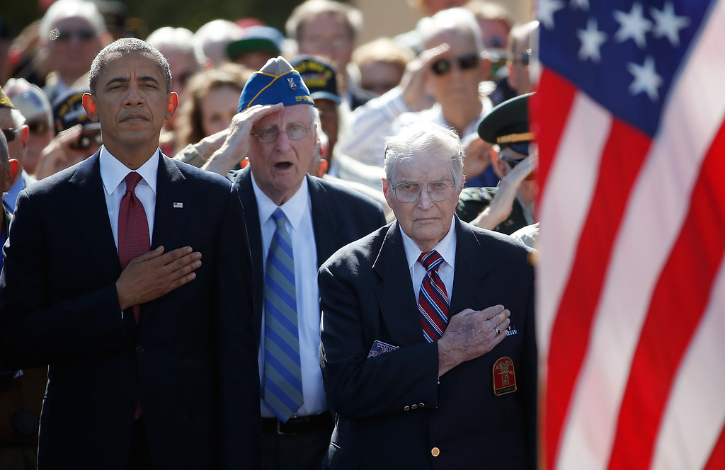 Description of . U.S. President Barack Obama joins WWII Veterans during the playing of the national anthem at a ceremony at the Normandy American Cemetery on the 70th anniversary of D-Day June 6, 2014 in Colleville-sur-Mer, France.  (Photo by Win McNamee/Getty Images)