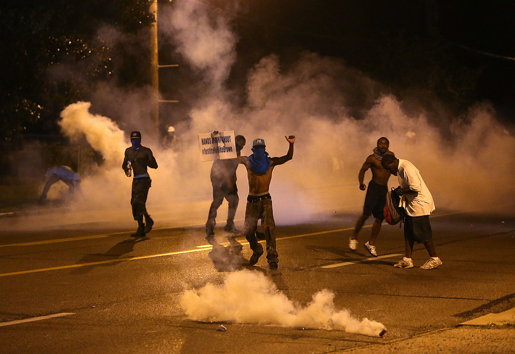 Description of . People protest as tear gas canisters detonate around them on Wednesday, Aug. 13, 2014, in Ferguson, Mo. Protests in the St. Louis suburb rocked by racial unrest since a white police officer shot an unarmed black teenager to death turned violent Wednesday night, with people lobbing molotov cocktails at police who responded with smoke bombs and tear gas to disperse the crowd. (AP Photo/St. Louis Post-Dispatch, Chris Lee)