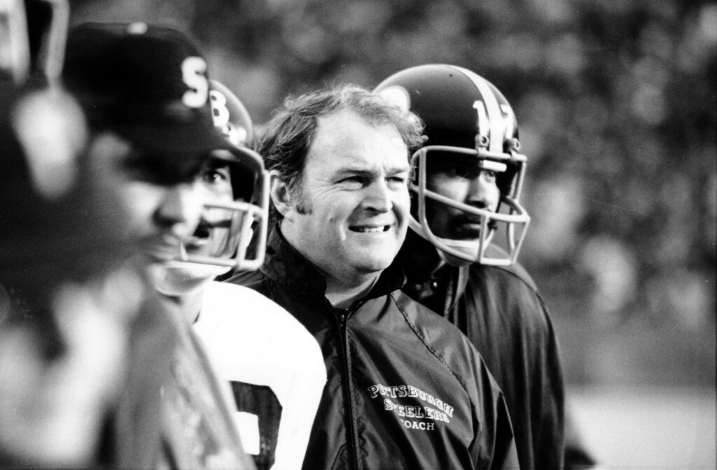 Description of . Pittsburgh Steelers coach Chuck Noll smiles as he watches his team play to a 16-6 victory over the Minnesota Vikings during the Super Bowl IX game at Tulane Stadium in New Orleans, La., on Jan. 12, 1975.  At right is Joe Gilliam (17).  (AP Photo)