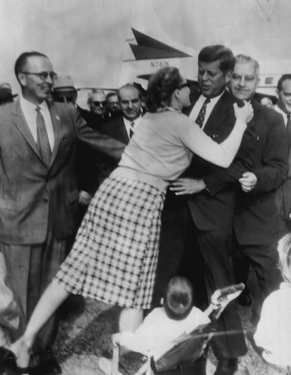 Description of . A surprised Sen. Kennedy gets Mrs. Alice Kruk's unqualified support at Niagara Falls Airport on Oct. 16, 1960. The tall, handsome, blond mother, with two of her three children watching in amazement, threw her arms around the presidential candidate and kissed him soundly. Associated Press file