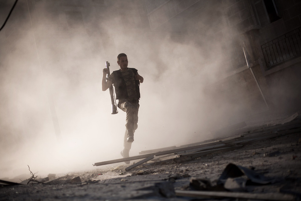 Description of . FILE - A Free Syrian Army fighter runs after attacking a tank with a rocket-propelled grenade during fighting in the Izaa district in Aleppo, Syria, Friday, Sept 7, 2012. (AP Photo/Manu Brabo, File)