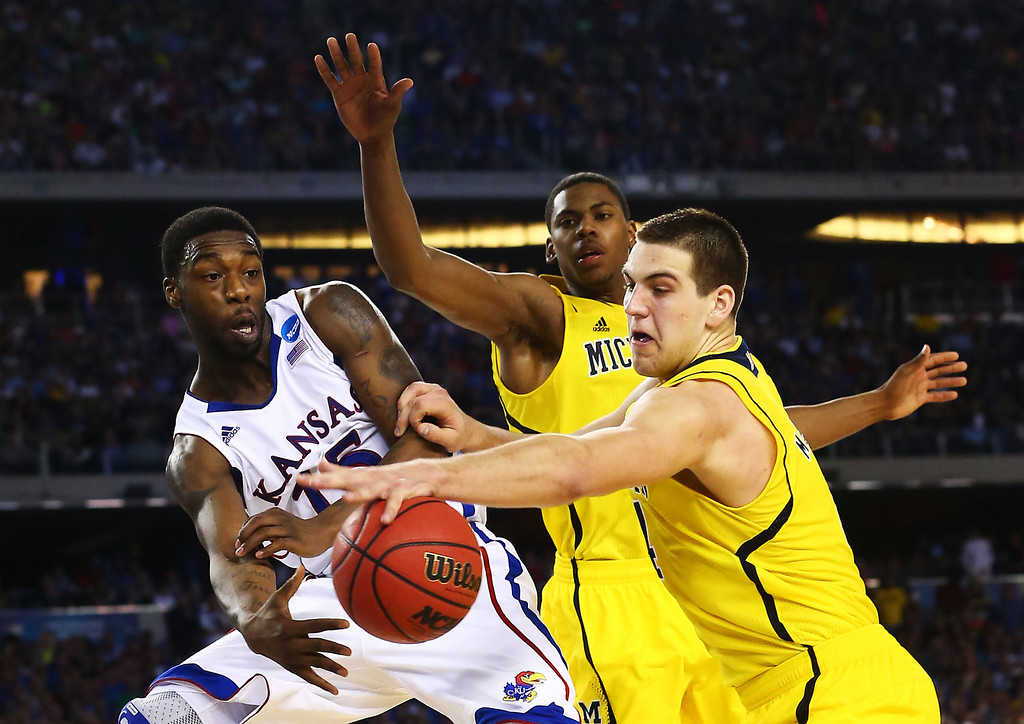 Description of . ARLINGTON, TX - MARCH 29:  Elijah Johnson #15 of the Kansas Jayhawks passes around Trey Burke #3 of the Michigan Wolverines in overtime during the South Regional Semifinal round of the 2013 NCAA Men\'s Basketball Tournament at Dallas Cowboys Stadium on March 29, 2013 in Arlington, Texas.  (Photo by Ronald Martinez/Getty Images)