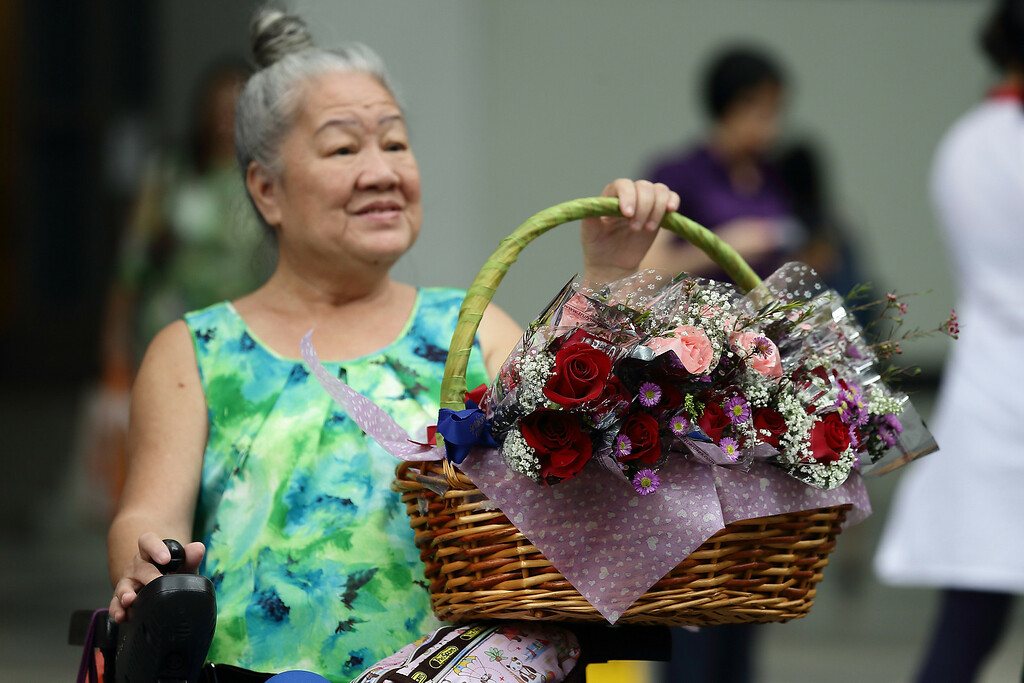 Description of . A wheelchair bound elderly woman sells flowers during Valentine's Day at Raffles Place on 14 February, 2013 in Singapore. Valentine's Day is a time to celebrate love, romance and friendship and is celebrated worldwide annually in different ways on February 14. (Photo by Suhaimi Abdullah/Getty Images)