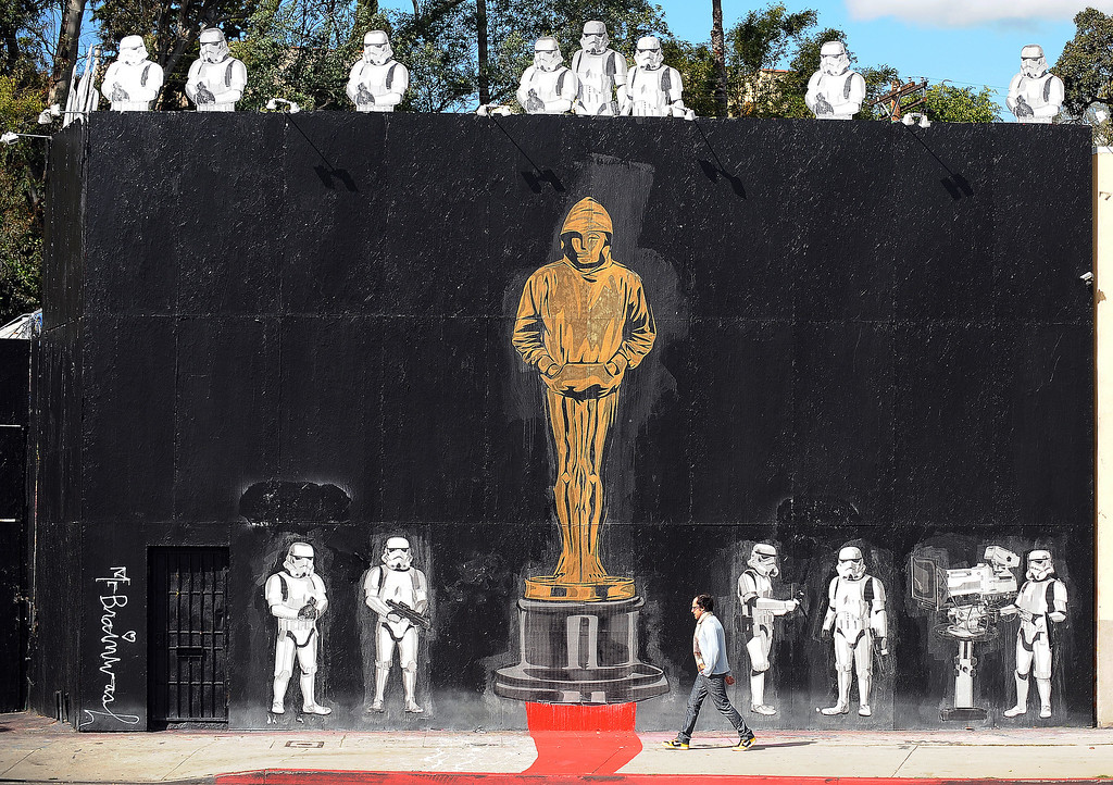 Description of . A man walks in front of a mural celebrating Banksy's Academy Award achievement signed by Mr. Brainwash in Los Angeles, California on February 17, 2011. Banksy is nominated for best documentary for