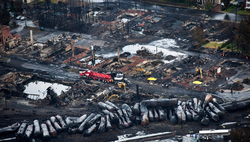 Description of . FOR USE AS DESIRED, YEAR END PHOTOS - FILE - Workers comb through debris Tuesday, July 9, 2013, after a train derailed Saturday causing explosions of railway cars carrying crude oil in Lac-Megantic, Quebec. (AP Photo/The Canadian Press, Paul Chiasson, File)