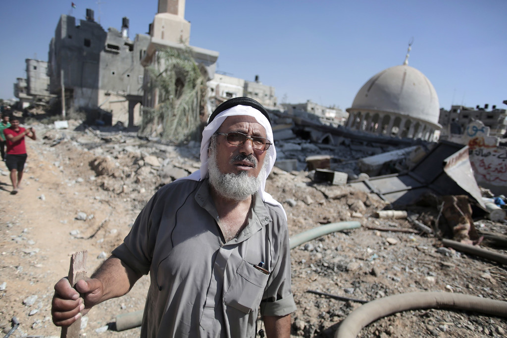 Description of . An elderly Palestinian man looks at the destruction caused by Israeli strikes in the village of Khuzaa, southern Gaza Strip, close to the Israeli border, Friday, Aug. 1, 2014. A three-day Gaza cease-fire that began Friday quickly unraveled, with Israel and Hamas accusing each other of violating the truce. (AP Photo/Khalil Hamra)