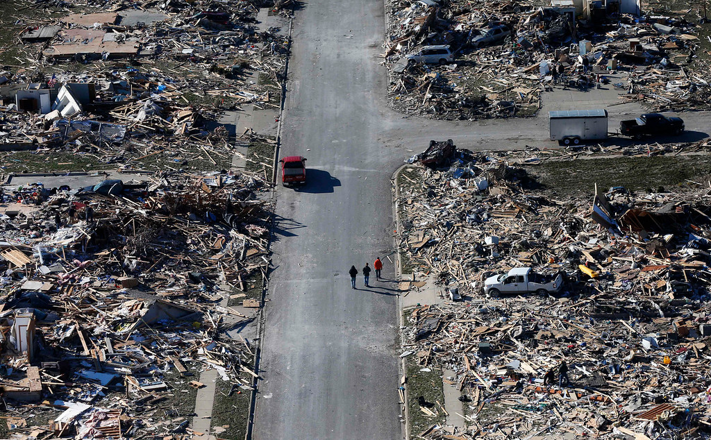 Description of . This aerial view on Monday, Nov. 18, 2013, shows people walking down a street where homes once stood that were  destroyed by a tornado that hit the western Illinois town of Washington. It was one of the worst-hit areas after intense storms and tornadoes swept through Illinois. The National Weather Service says the tornado that hit Washington had a preliminary rating of EF-4, meaning wind speeds of 170 mph to 190 mph. (AP Photo/Charles Rex Arbogast)