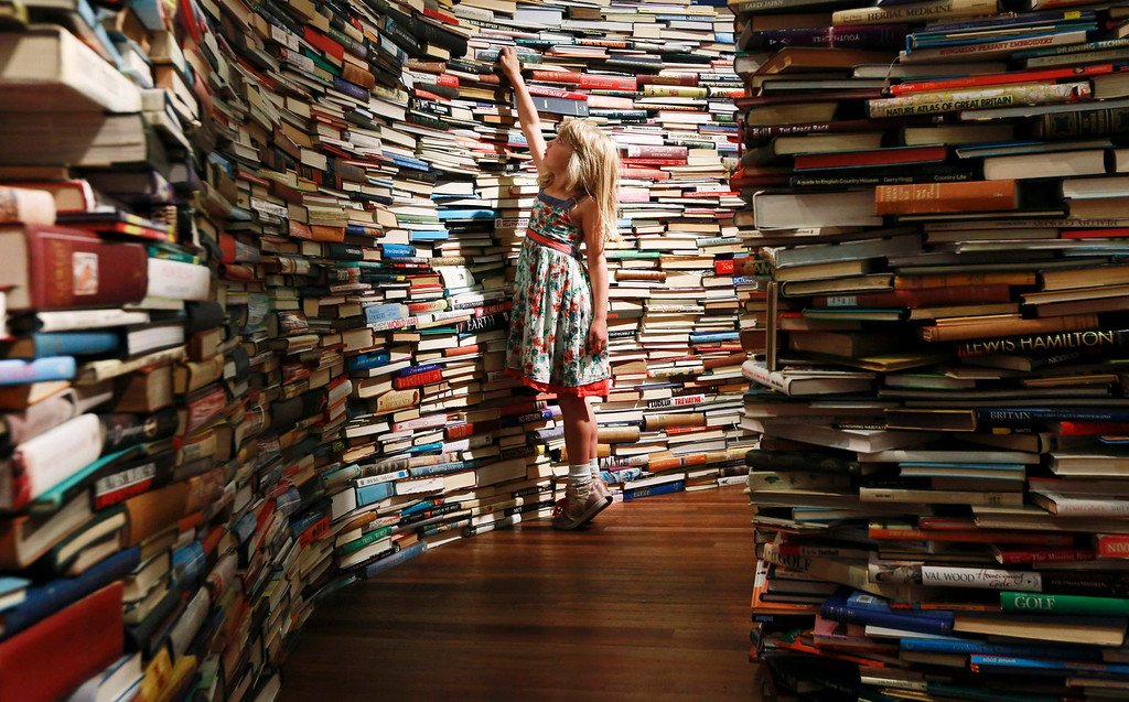 Description of . Leona, 7, poses inside a labyrinth installation made up of 250,000 books titled