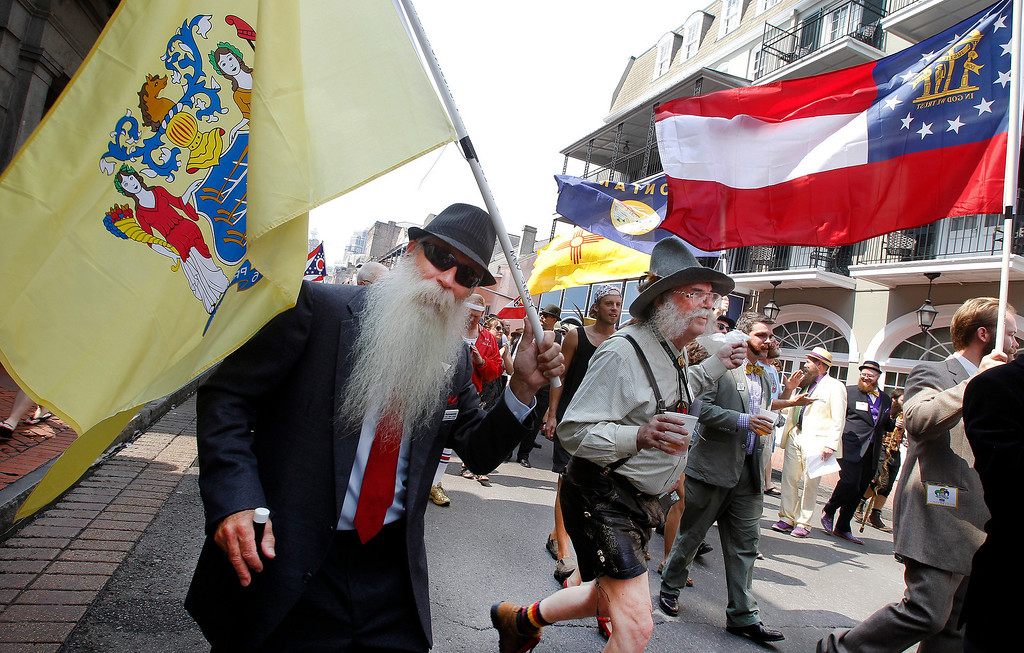 Description of . Chris Porrovecchio of Kendall Park, New Jersey ,left, carries the New Jersey state flag during a parade through the French Quarter kicking off the fourth annual Just For Men National Beard and Moustache Championships Saturday, September 7, 2013 in New Orleans. Contestants competed in 18 different categories including Dali, full beard natural and sideburns.  (AP Photo/Susan Poag)