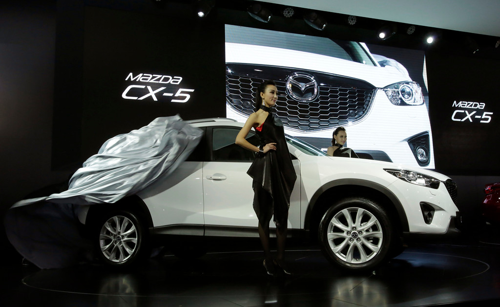 Description of . Mazda's new CX-5 is unveiled at the Shanghai International Automobile Industry Exhibition (AUTO Shanghai) media day in Shanghai, China, Saturday, April 20, 2013. (AP Photo/Eugene Hoshiko)