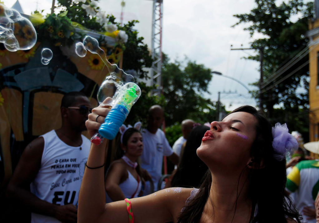 Description of . A reveller blows bubbles during the annual block party known as the