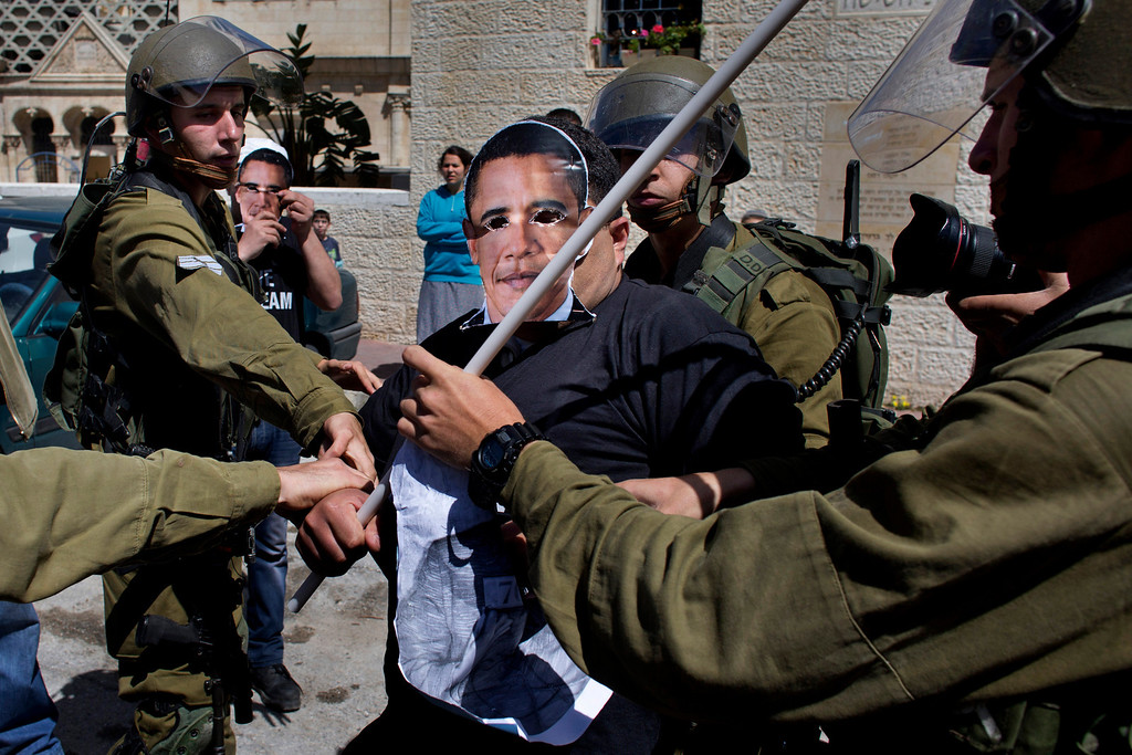 Description of . Israeli soldiers scuffle with a Palestinian activist wearing a mask of U.S. President Barack Obama during a protest in the West Bank town of Hebron, Wednesday, March 20, 2013. (AP Photo/Bernat Armangue)
