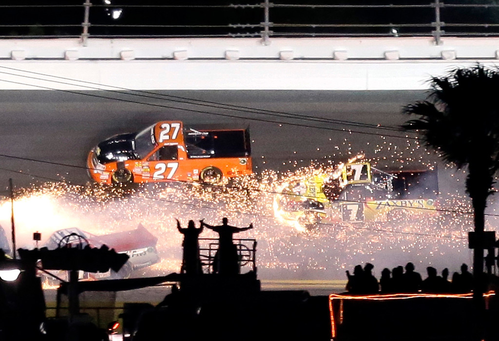 Description of . John Wes Townley (7) drives into a shower of sparks as he avoids Jeff Agnew (27) during a crash in the NASCAR Truck Series auto race Friday, Feb. 22, 2013, at Daytona International Speedway in Daytona Beach, Fla. (AP Photo/Chris O'Meara)