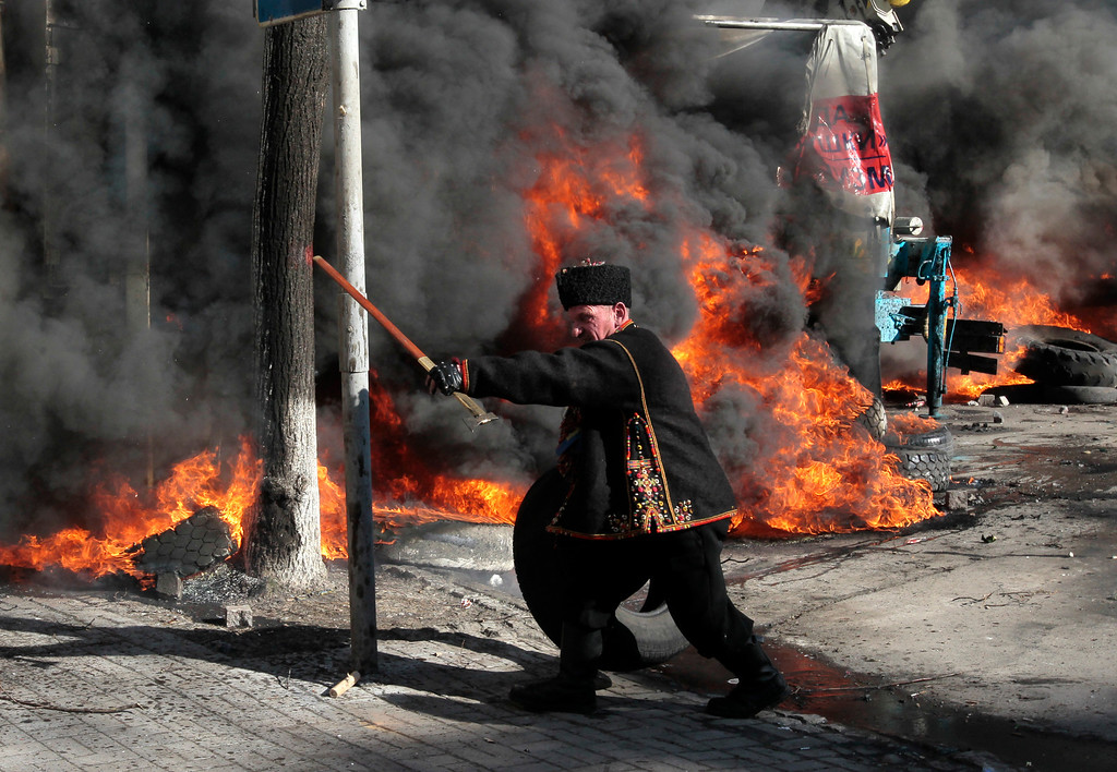 Description of . An anti-government protester threatens riot police outside Ukraine's parliament in Kiev, Ukraine, Tuesday, Feb. 18, 2014. (AP Photo/Sergei Chuzavkov)