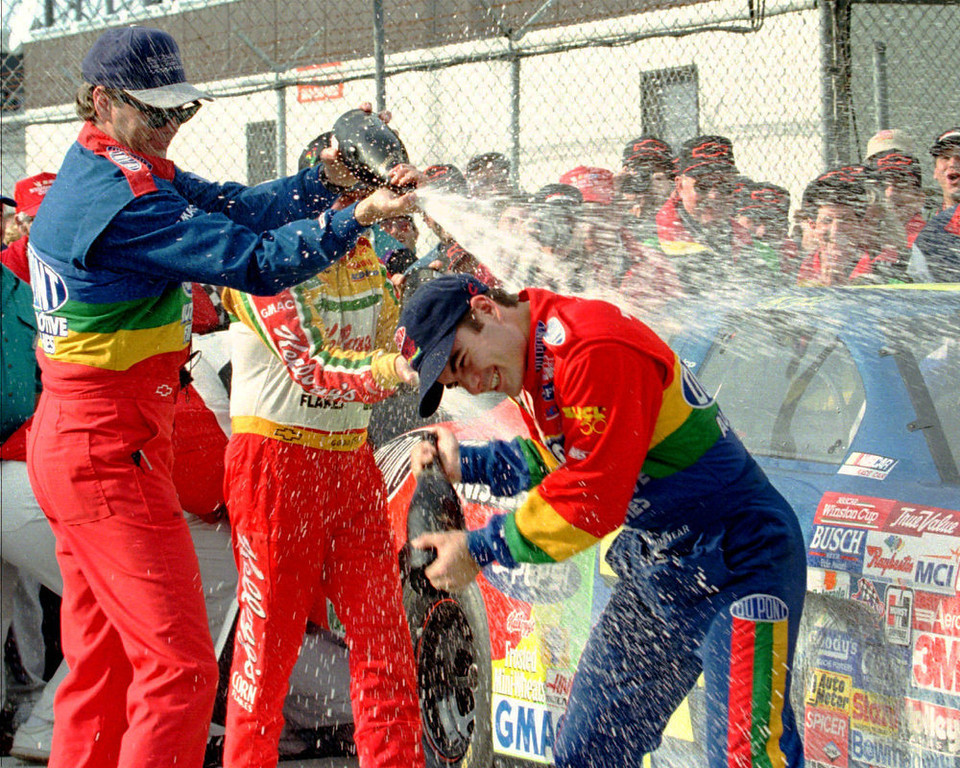 Description of . Daytona 500 winner Jeff Gordon, from Pittsboro, Ind., right, is showered with champagne by DuPont Refinishes Chevrolet crew chief Ray Evernham, left, and Terry Labonte in Victory Lane Sunday afternoon Feb. 16, 1997 at Daytona International Speedway in Daytona Beach, Fla. (AP Photo/Terry Renna)