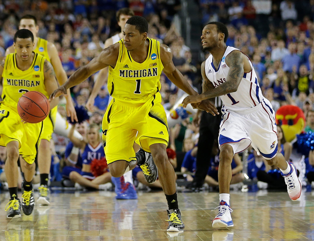 Description of . Michigan\'s Glenn Robinson III steals the ball from Kansas\' Naadir Tharpe during overtime of a regional semifinal game in the NCAA college basketball tournament, Friday, March 29, 2013, in Arlington, Texas. (AP Photo/David J. Phillip)