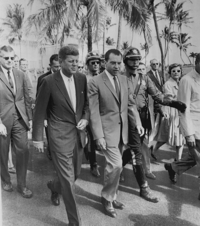Description of . President-elect Kennedy and Vice President Richard Nixon walk with security guards and admirers through the grounds of the Key Biscayne Hotel on Nov. 14, 1960, after meeting for a post-campaign conference. Denver Post file
