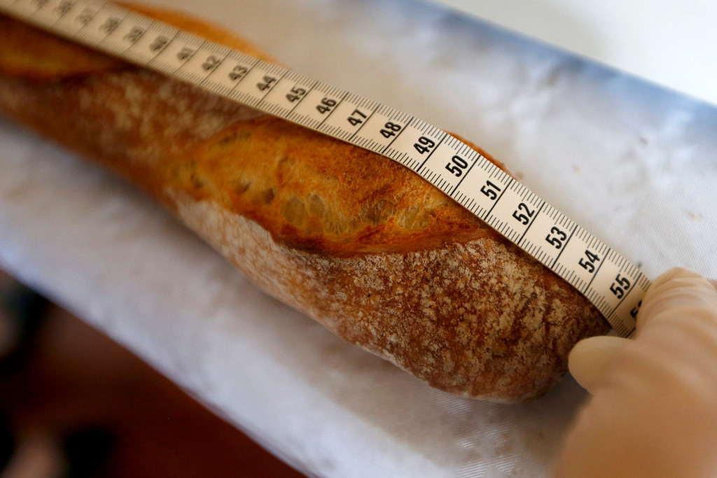 Description of . An assistant measures a baguette registered in the competition for the 'Grand Prix de la Baguette de la Ville de Paris' (Best Baguette of Paris 2013) annual prize at the Chambre Professionnelle des Artisans Boulangers Patissiers in Paris April 25, 2013. The baguette is a French cultural symbol par excellence and the competition saw 203 Parisian bakers who compete for recognition as finest purveyor of one of France's most iconic staples. The baguettes are registered, given anonymous white wrappings and an identification number. They are then carefully weighed and measured to ensure they do not violate the contest's strict rules. 52 entries were withdrawn for failing to measure between 55-70cm long or not matching the acceptable weight of between 250-300g. Every year, the winner earns the privilege of baking bread for the French President.   REUTERS/Charles Platiau