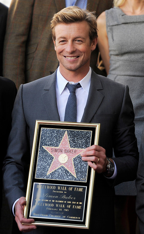 . Australian actor Simon Baker holds a replica of his new star on the Hollywood Walk of Fame, on Thursday, Feb. 14, 2013 in Los Angeles. (Photo by Chris Pizzello/Invision/AP)