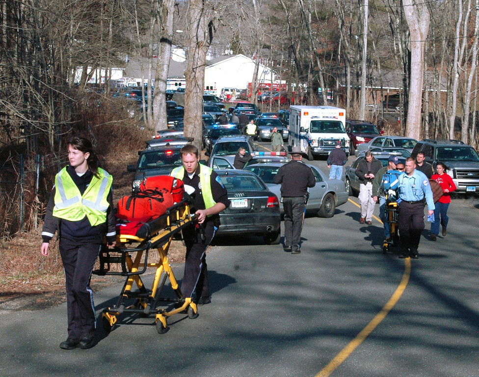 Description of . In this photo provided by the Newtown Bee, paramedics push stretchers toward Sandy Hook Elementary School in Newtown, Conn., where authorities say a gunman opened fire, killing 26 people, including 20 children, Friday, Dec. 14, 2012. (AP Photo/Newtown Bee, Shannon Hicks)
