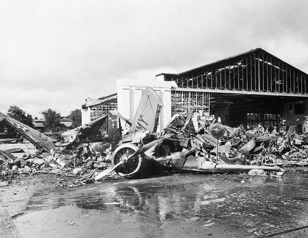 Description of . In this photo provided by the Department of Defense, U.S. aircraft destroyed as a result of the Japanese bombing on Pearl Harbor is shown, Dec. 7, 1941. Heap of demolished hanger in background Army amphibian in foreground. (AP Photo/DOD)