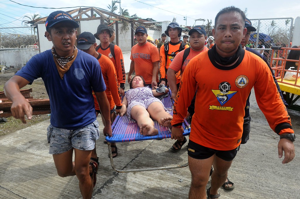 Description of . Rescue workers carry a woman about to give birth at a makeshift Department of Health (DOH) medical center at the Tacloban airport in the aftermath of Super Typhoon Haiyan in Tacloban, eastern island of Leyte on November 9, 2013. One of the strongest typhoons on record killed more than 100 people as savage winds and giant waves flattened communities across the Philippines, authorities said on November 9 while corpses lay amid the devastation. NOEL CELIS/AFP/Getty Images