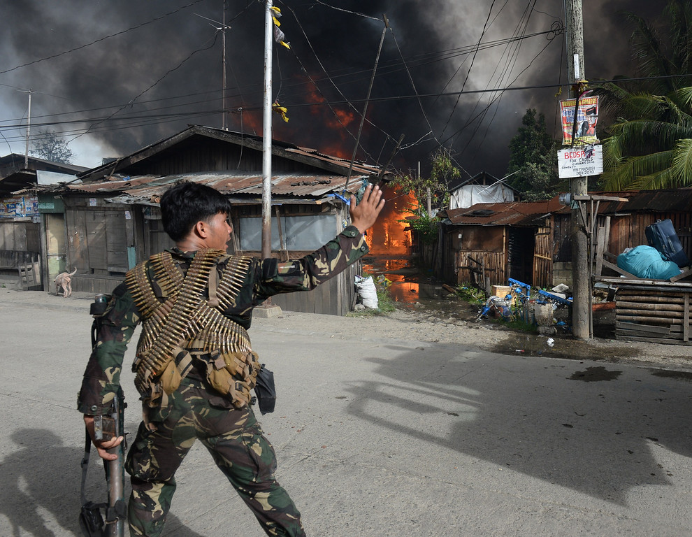 Description of . A Philippine soldier guides a fire truck to burning houses during a fire fight between government forces and Muslim rebels as stand-off entered its fourth day in Zamboanga City on the southern island of Mindanao on September 12, 2013.  AFP PHOTO/TED ALJIBE/AFP/Getty Images