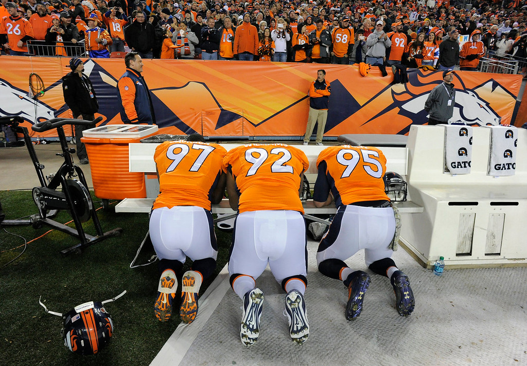 Description of . Denver Broncos defensive end Malik Jackson (97), Denver Broncos defensive tackle Sylvester Williams (92) and Denver Broncos defensive end Derek Wolfe (95) take a moment before the start of the game. The Denver Broncos take on the Kansas City Chiefs at Sports Authority Field at Mile High in Denver on November 17, 2013. (Photo by John Leyba/The Denver Post)