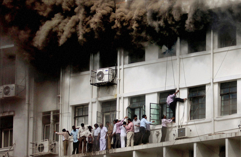 Description of . In this June 21, 2012 file photo, Indian employees are evacuated as smoke billows after the Maharashtra state government building caught fire in Mumbai, India. Hundreds of employees were evacuated from the seven-story government building as more than two dozen fire engines battled the major fire that raged for more than three hours in India's financial and entertainment capital. (AP Photo/File)