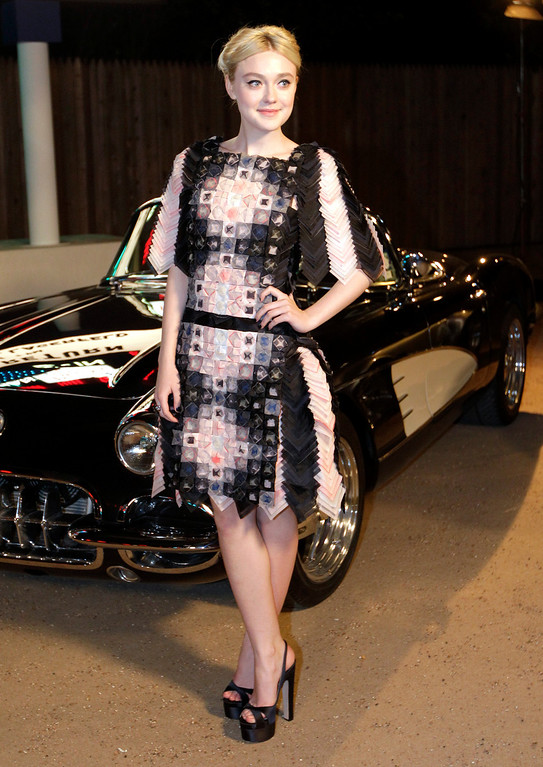 Description of . Actress Dakota Fanning poses for photos after arriving for Chanel's Metiers d'Art fashion show, Tuesday, Dec. 10, 2013, in Dallas. (AP Photo/Tony Gutierrez)